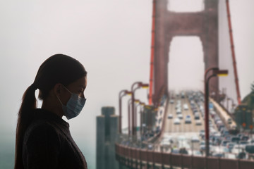 Coronavirus in California. Woman with surgical mask for corona virus covid-19 protection in San Francisco, USA, in front of Golden Gate Bridge. California, America.