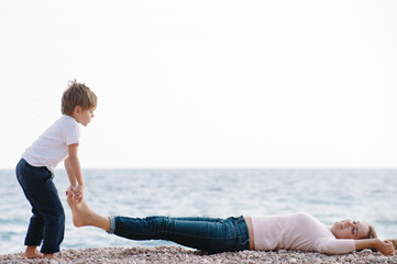 funny active small boy lifting his mother lying on sea beach legs during spring leisure outdoor recreation games with copy space Wall mural