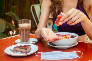 woman useing antibacterial gel on hands before start to eating her healthy food in tropical asian cafe . smoothie bowl , raw cake and coffee on table with sanitizer on bottle