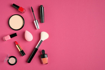 Makeup products and cosmetics on pink background. Flat lay, top view. Beauty and fashion concept.