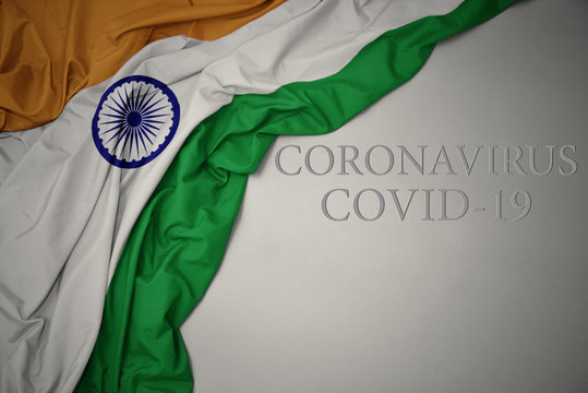 waving national flag of india on a gray background with text coronavirus covid-19 . concept.