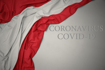 waving national flag of austria on a gray background with text coronavirus covid-19 . concept. Fototapete
