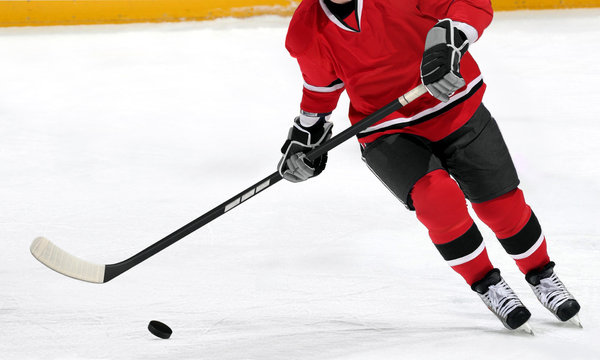 Ice hockey player dribbling puck on rink