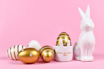 Golden and white painted easter eggs with dots and stripes, cute easter egg cup in shape of bunny and rabbit figure on pink background