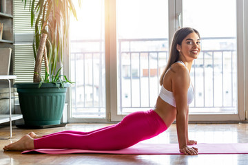 Photo of a beautiful female stretching on the floor sitting on a mat. Young beautifull woman stretching on the floor. Home training exercises, work out from home