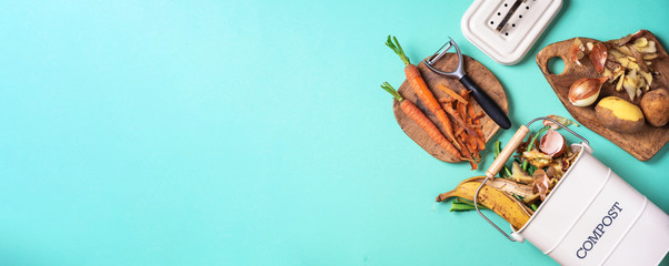 Peeled vegetables in white compost bin on blue background. Trash bin for composting with leftover from kitchen on blue background. Top view. Recycling scarps concept. Sustainable and zero waste
