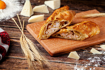 Baking Georgian cuisine. Puff pastry pie with chicken and cheese. The dish lies on a wooden table. background image, copy space text Fototapete