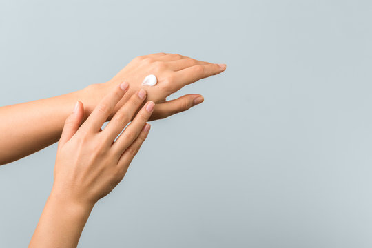 closeup of tender hands of a young woman with moisturizer on. spring skin protection