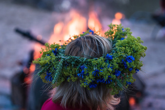 at the campfire with a wreath on the head, blue cornflowers inside the summer solstice wreath, along with other field flowers and plants