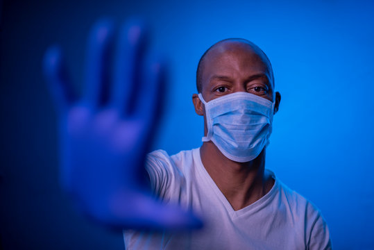 STOP Coronavirus, African American man shows the stop coronavirus sign, wearing protective mask and gloves on blue background in studio. Focus on face. COVID-19 concept.