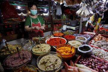 A vendor wears a face mask as she prepares to sell spices at a traditional market amid the spread of coronavirus disease (COVID-19) in Jakarta