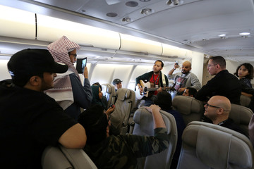 Saudi youth plays musical instrument on board a plane during a flight to al-Ula, to attend the Tantura Festival