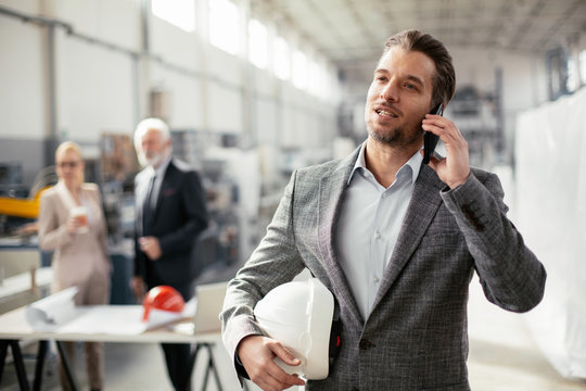 Young businessman using phone. Businessman talking to smart phone.