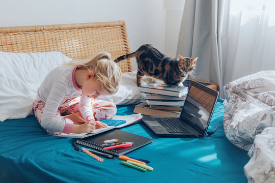 Caucasian girl child sitting in a bed and learning online on laptop Internet. Virtual class lesson on video during self isolation at home. Distant remote video education. Modern school study for kids.