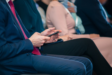 A man at a business conference sits with a smartphone