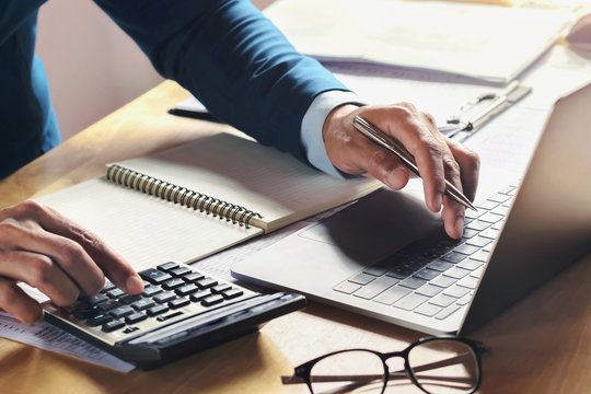 businessman working on desk with using calculator and computer in office. concept accounting finance