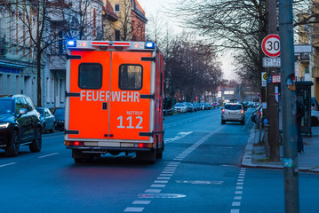 Ambulance photographed from behind, blue lights, Berlin fire brigade