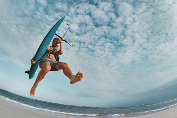 Kite surfer jumps with wakeboard