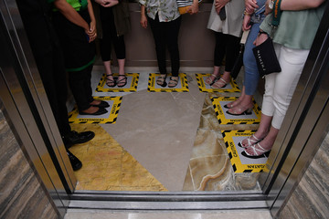 Visitors stand on boxes for social distancing inside an elevator at a shopping mall amid the spread of coronavirus disease (COVID-19) in Surabaya