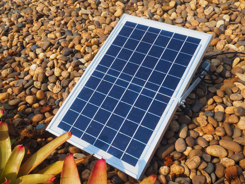 blue solar panel system on brown and black rock in the garden using for energy saving concept