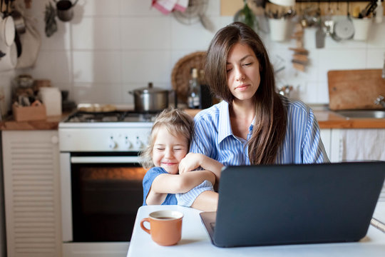 Working from home with kid. Happy daughter hugging mother. Young woman and cute child using laptop. Freelancer workplace in cozy kitchen. Female business, distance learning. Lifestyle family moment.