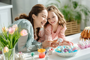 adorable child and happy mother near chicken eggs, decorative rabbits, easter bread and tulips