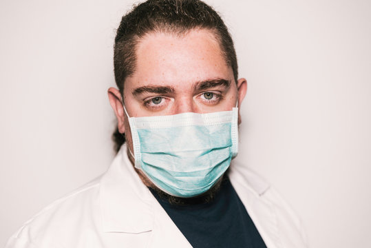 Medical stock photography wearing blue mask and white coat with green eyes.