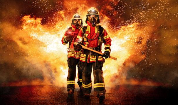 Zwei Feuerwehrmänner unter Atemschutz gehen durchs Feuer