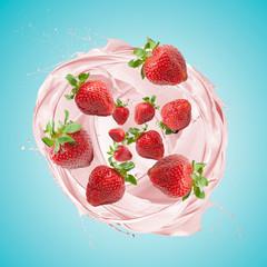 Fototapete - Strawberry milkshake splashing with fruits, on blue background