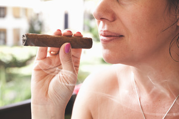 Hand of a young woman smoking handmade cigar