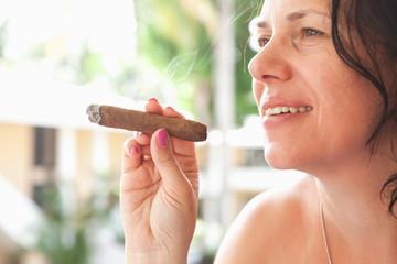 Young smiling woman smokes handmade cigar