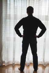 Tthinking man standing over big window with tulle