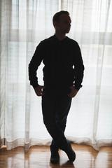 Silhouette photo of a man posing near bright window