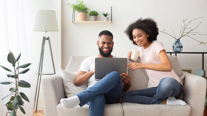 African american couple on couch with laptop - fototapety na wymiar