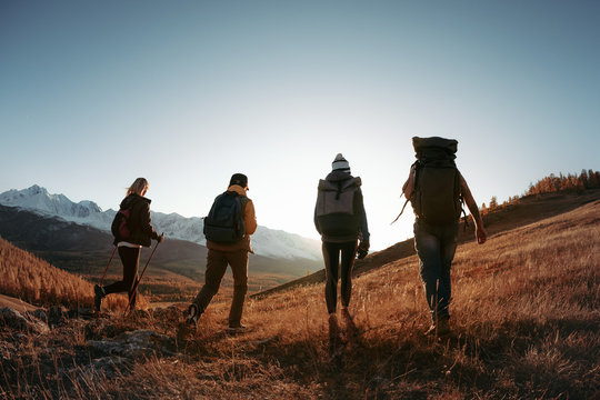 Four hikers or backpackers walks in sunset mountains