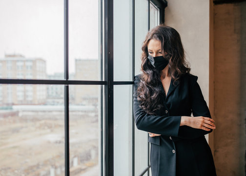 A woman in a medical mask looks out the window.