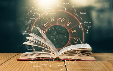 Wall Mural - Open book on old wooden table with astrology illustration