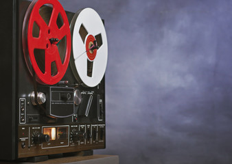 Vintage Reel to reel tape recorder on a grunge background with copy space . A symbol of recording in retro style