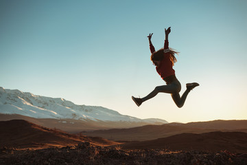 Happy girl jumps against mountains at sunset Fotomurales