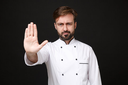 Displeased young bearded male chef cook or baker man in white uniform shirt posing isolated on black background in studio. Cooking food concept. Mock up copy space. Showing stop gesture with palm.