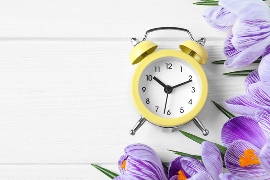 Yellow alarm clock, spring flowers and space for text on white wooden table, flat lay. Time change