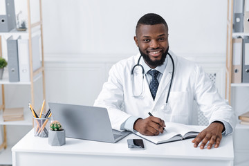 Smiling black doctor working with laptop in office