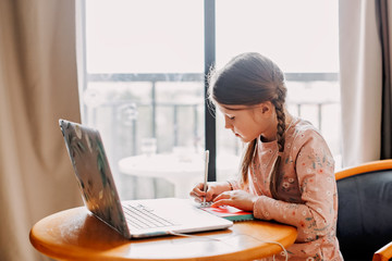 schoolgirl does homework laptop at home,quarantine