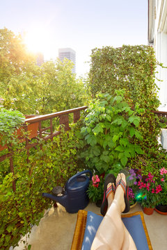 Home office in summer: woman's feet in flip-flops on a footrest on a city balcony with lots of plants.