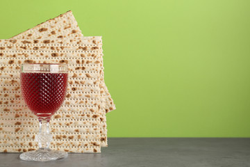 Passover matzos and glass of wine on grey table, space for text. Pesach celebration