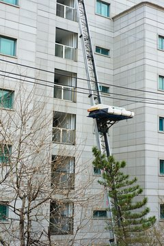 Moving mattresses and a box from a high floor of a building with a hydraulic hoist ladder