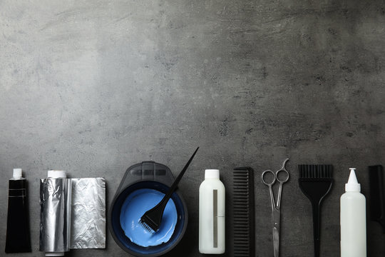 Professional tools for hair dyeing on grey stone background, flat lay. Space for text