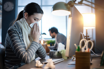 Woman working in the office and having a cold