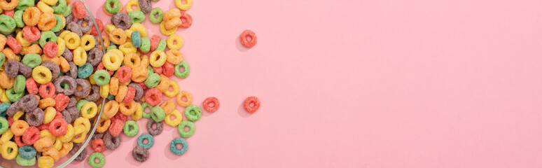 top view of bright colorful breakfast cereal scattered from bowl on pink background, panoramic shot Fotobehang