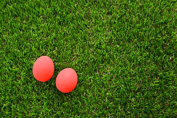 red easter egg on lawn green grass artificial, image background of morning springtime concept